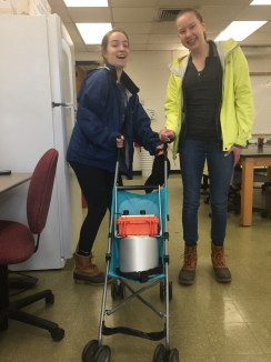 "Cameron Peters and Jennie VanMeter put ""the baby"" (soil CO2 fluxmeter) in the stroller for a walk down to their forest research sites at the BFEC."
