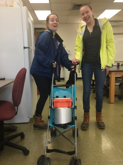 """Cameron Peters and Jennie VanMeter put """"the baby"""" (soil CO2 fluxmeter) in the stroller for a walk down to their forest research sites at the BFEC."""